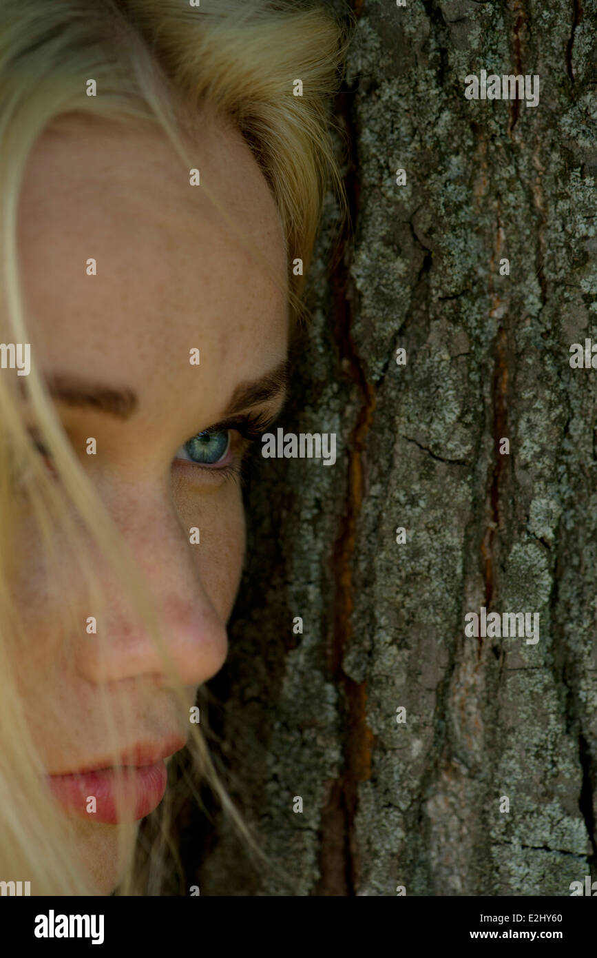 Young woman leaning against tree trunk, regardant ailleurs malheureusement Photo Stock