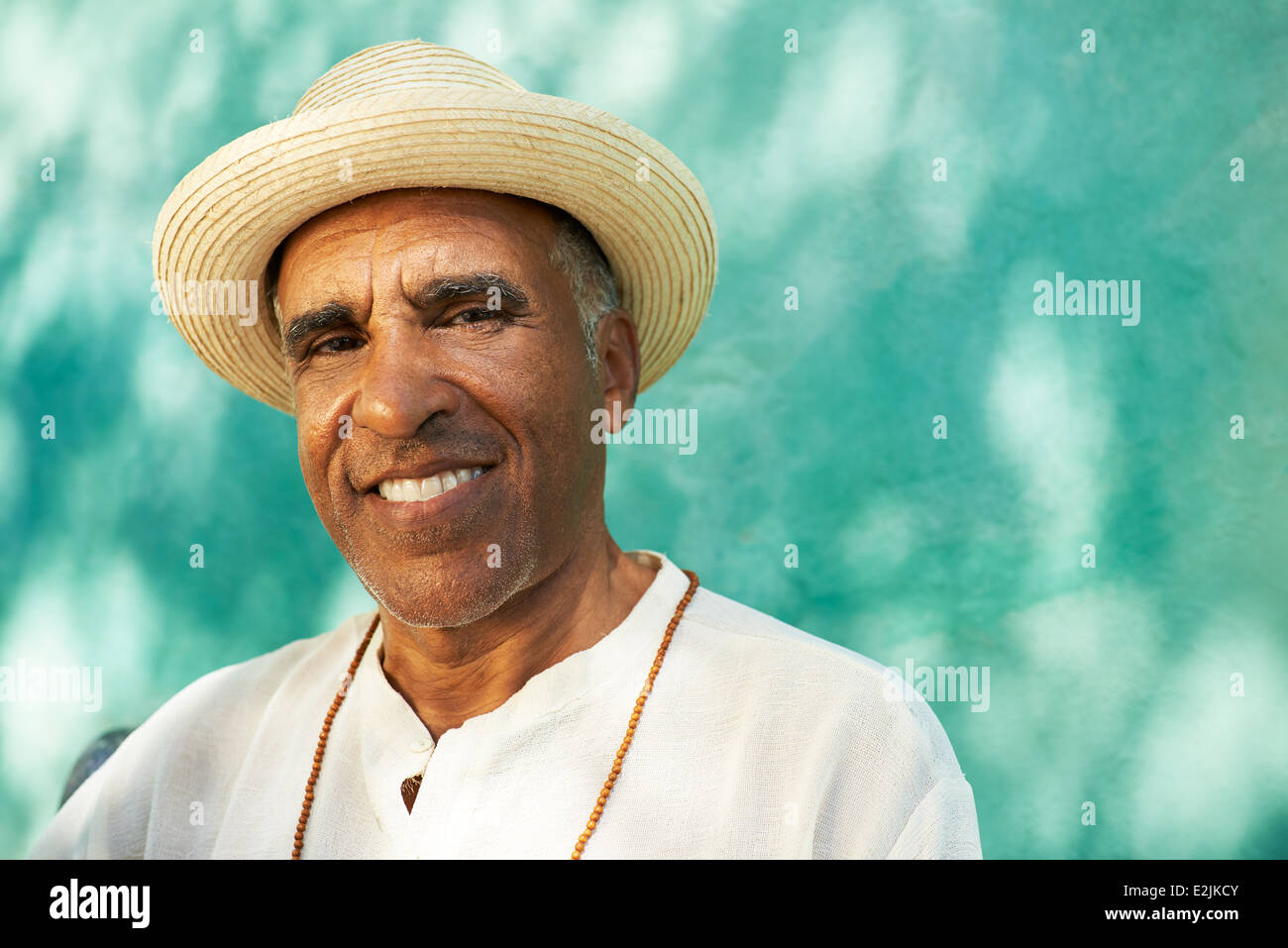 Portrait de senior retraité hispanic man with straw hat assis dans un parc et à la recherche à l'appareil Photo Stock