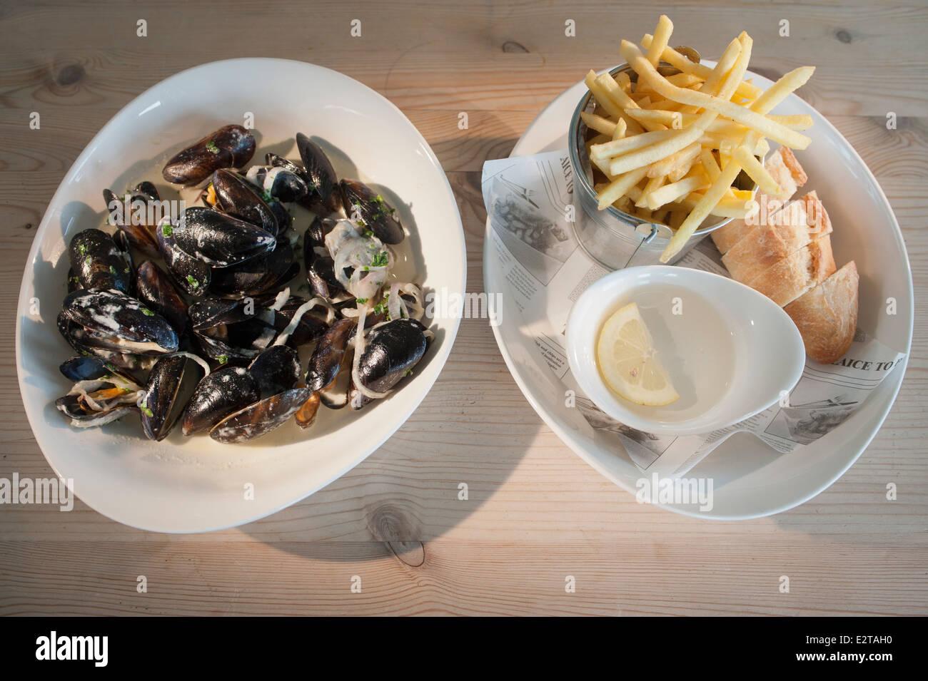 Des moules ou des moules cuites dans le vin blanc avec le persil et accompagnés de chips ou de frites et de Photo Stock