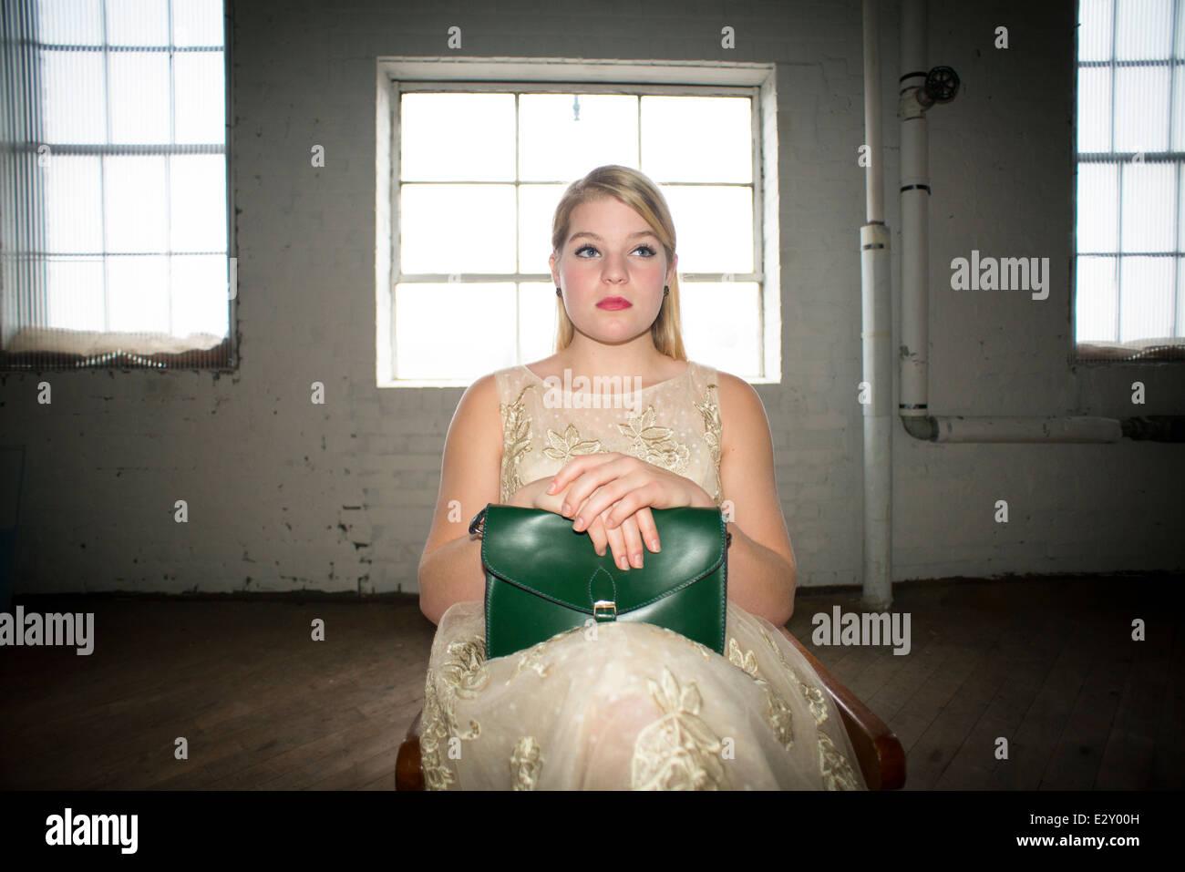 Un 16-year-old woman femme portant une robe en dentelle des années 60 tenant un sac à main vert vintage Photo Stock