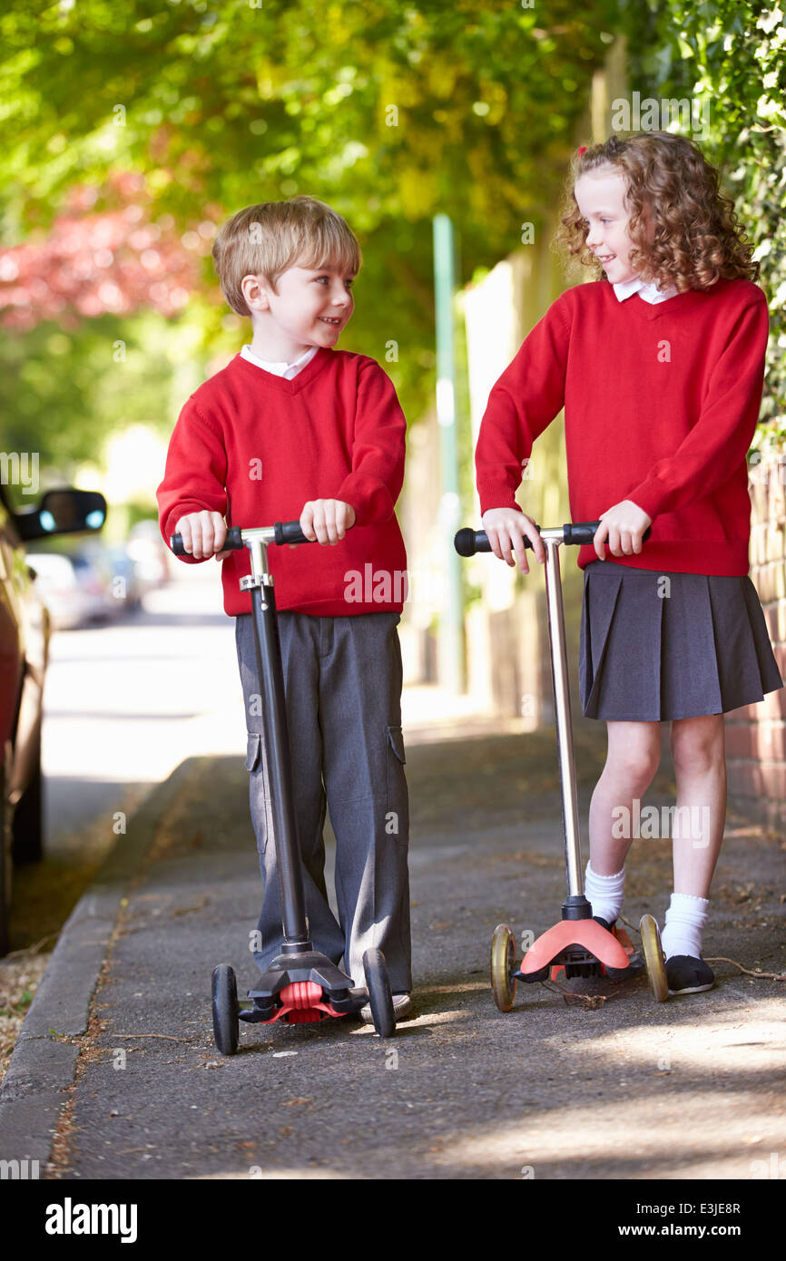 Boy and Girl Riding Scooter sur le chemin de l'école Photo Stock