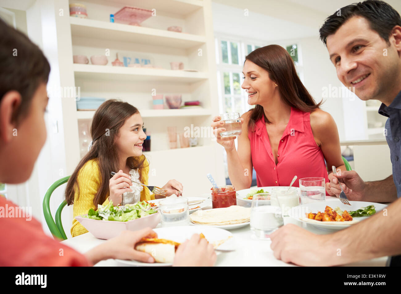 Hispanic Family Sitting At Table Eating Meal Together Banque D'Images
