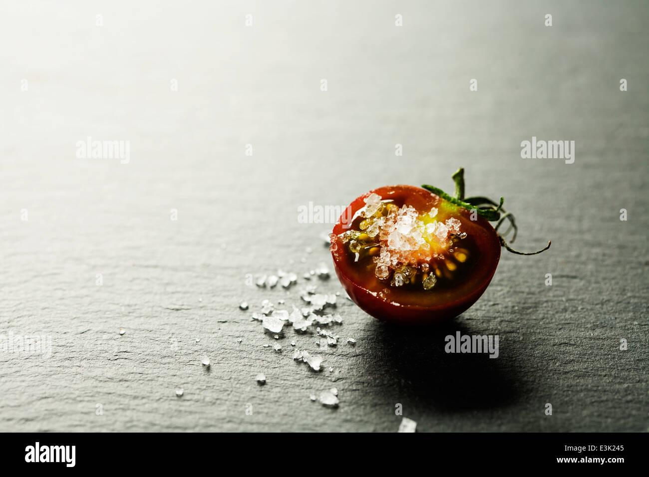 Tomates Raisins frais avec du sel pour une utilisation comme ingrédients de cuisson de moitié avec une Photo Stock