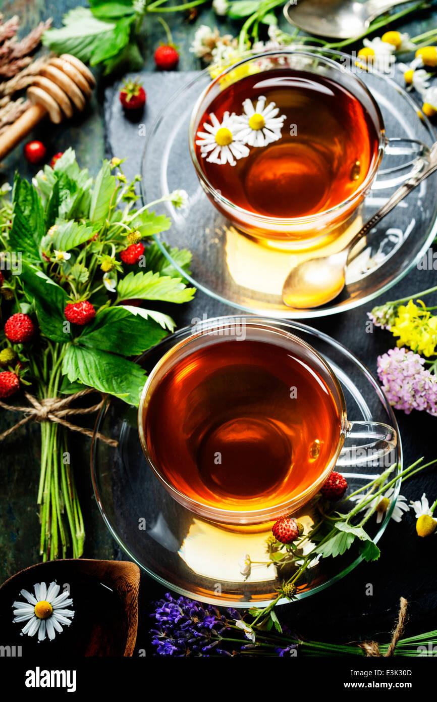 Une tisane avec du miel, des petits fruits sauvages et de fleurs sur fond de bois Photo Stock
