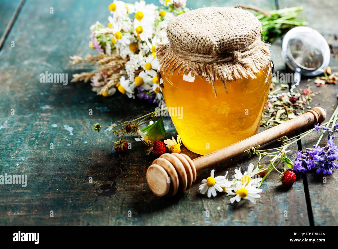 Le miel et le thé de fines herbes sur fond de bois - l'été, de la santé et de l'organic Photo Stock