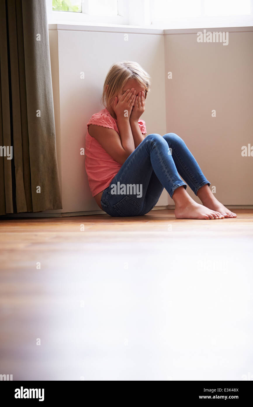 Malheureux enfant assis sur le plancher dans le coin à la maison Photo Stock