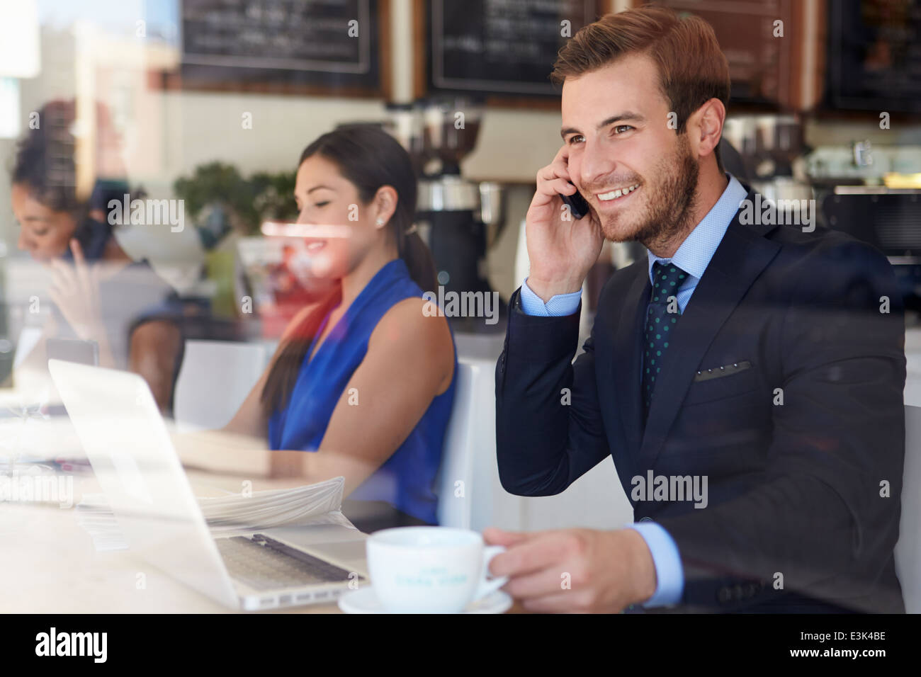 Businessman Using Mobile Phone and Laptop in Coffee Shop Banque D'Images