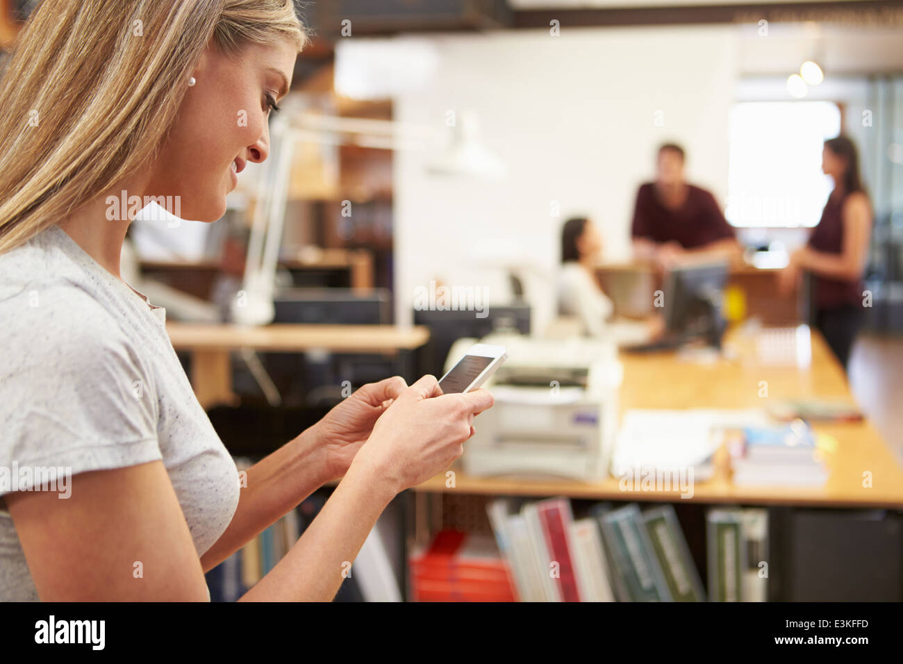 Businesswoman Using Mobile Phone In Modern Office Banque D'Images