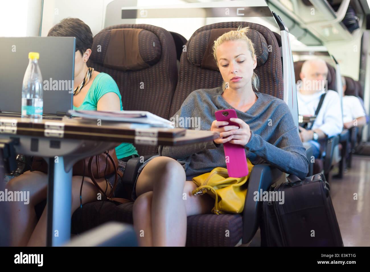 Dame voyageant par train à l'aide de votre smartphone. Photo Stock
