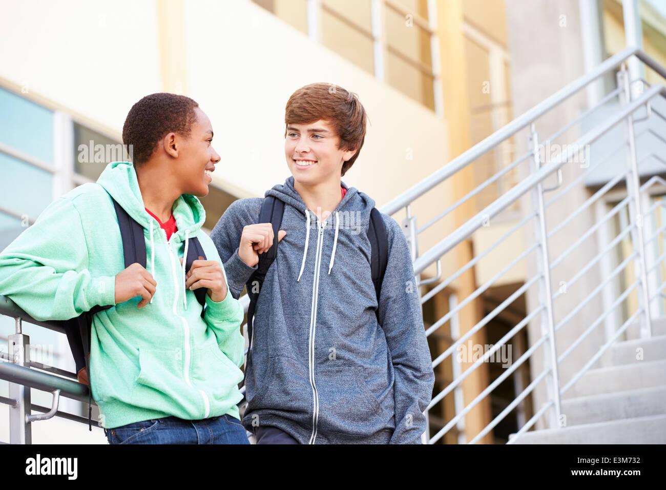Les élèves du secondaire, deux hommes debout à l'extérieur du bâtiment Photo Stock