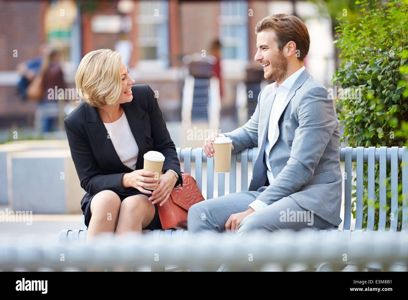 Business Couple sur banc de parc avec du café Banque D'Images