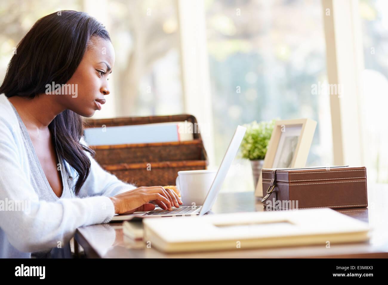 Femme à l'aide d'un ordinateur portable sur un bureau à la maison Photo Stock