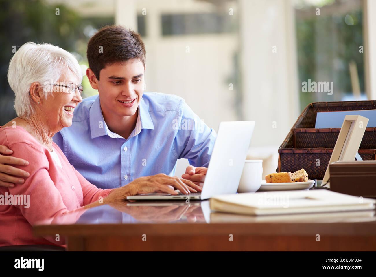 Petit-fils d'Adolescent aider grand-mère avec portable Photo Stock