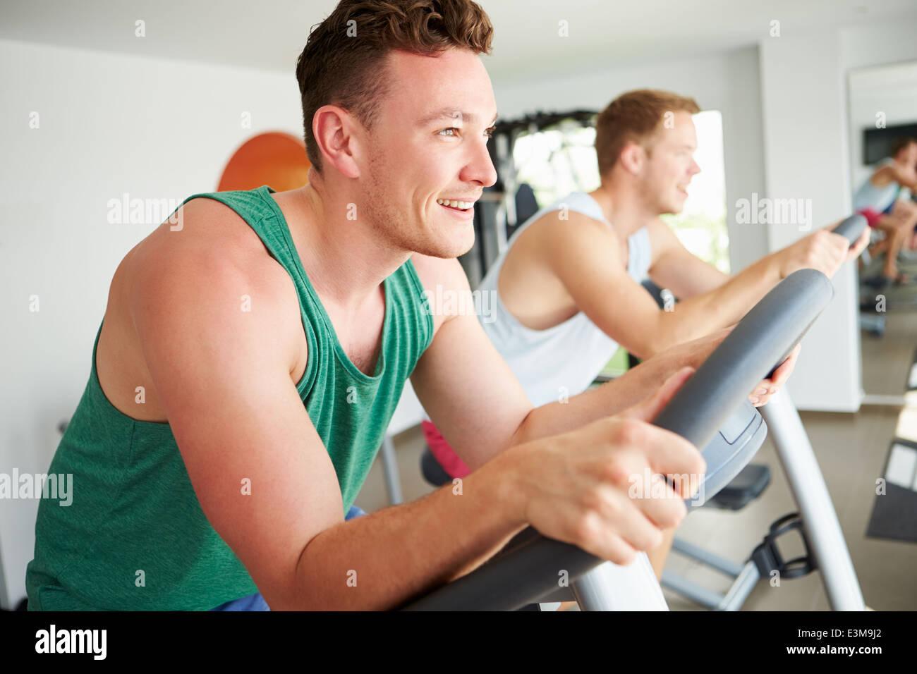 Deux jeunes hommes en formation sur l'ensemble des machines de Sport cyclisme Photo Stock