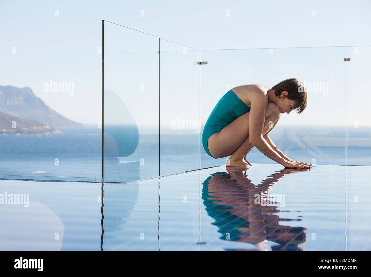 Femme accroupie au-dessus d'une piscine à débordement avec vue sur l'océan Banque D'Images