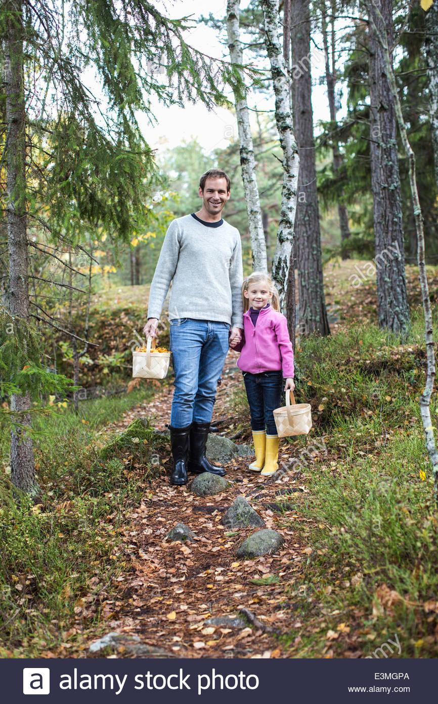 Portrait de père et fille portant des paniers en forêt Photo Stock