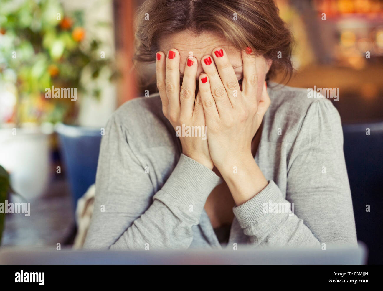 Sad woman with head in hands at home Photo Stock