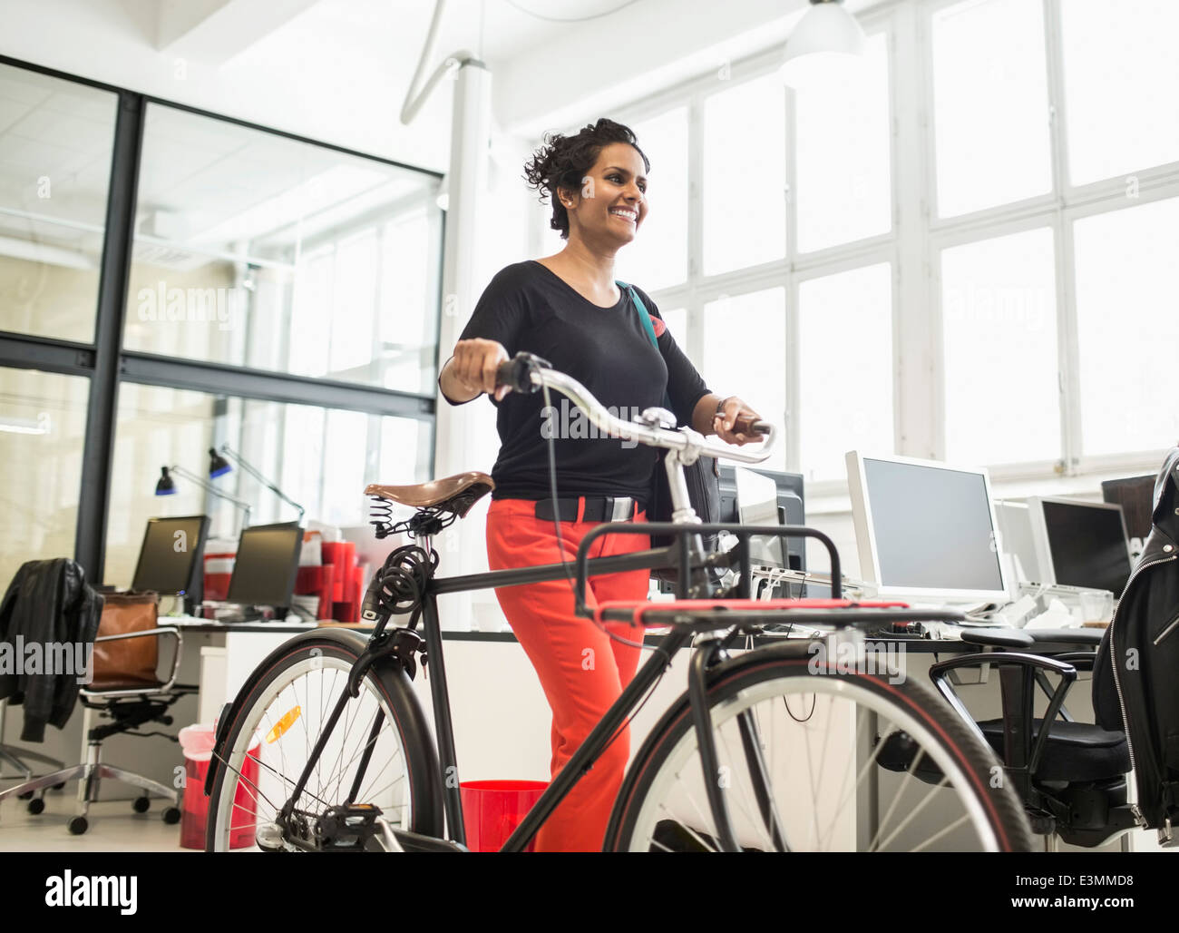 Smiling businesswoman with location walking in creative office Photo Stock