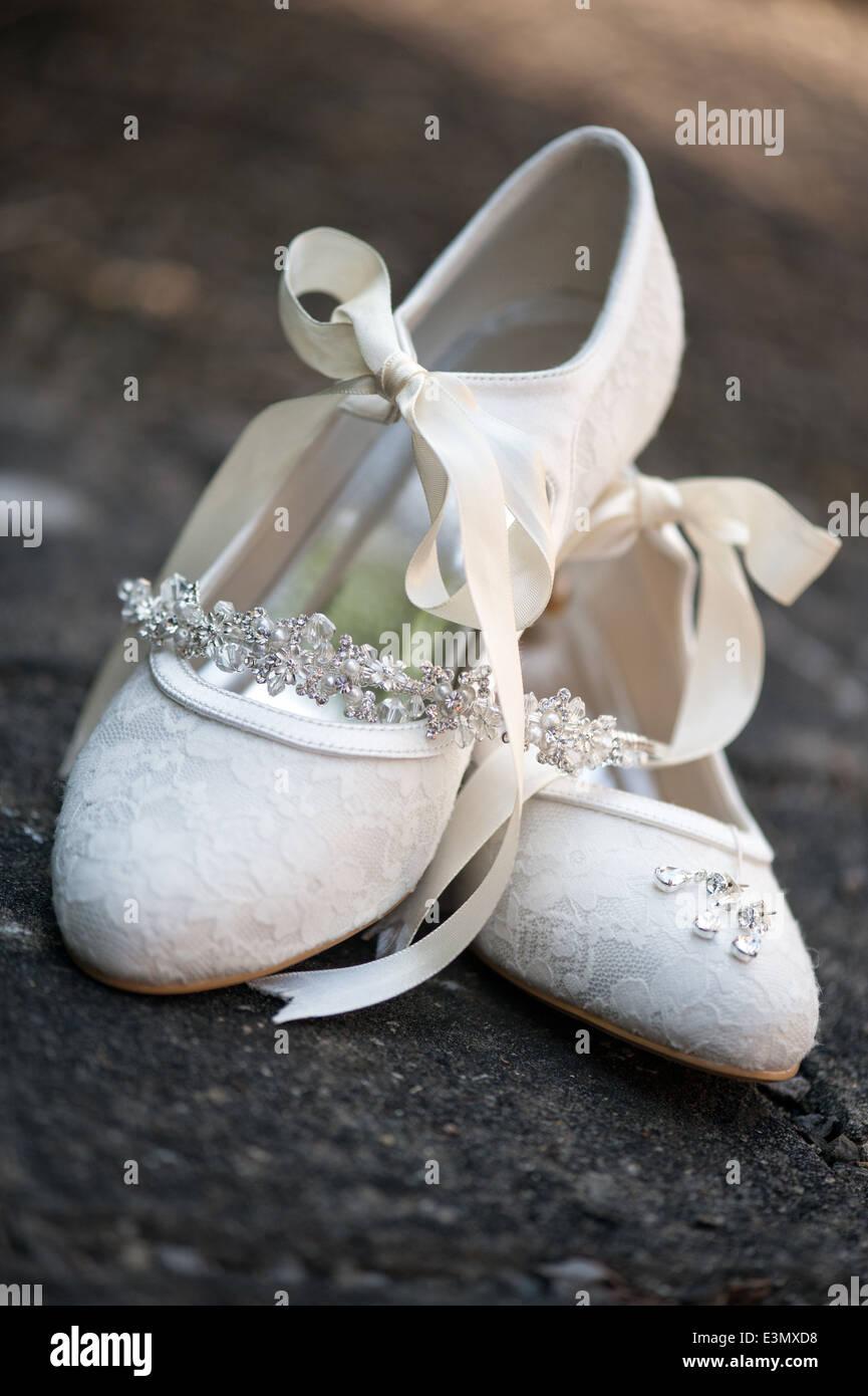 Une paire de brides blanc antique, ruban noué chaussures de mariage posées avec les Bijoux de mariée Photo Stock