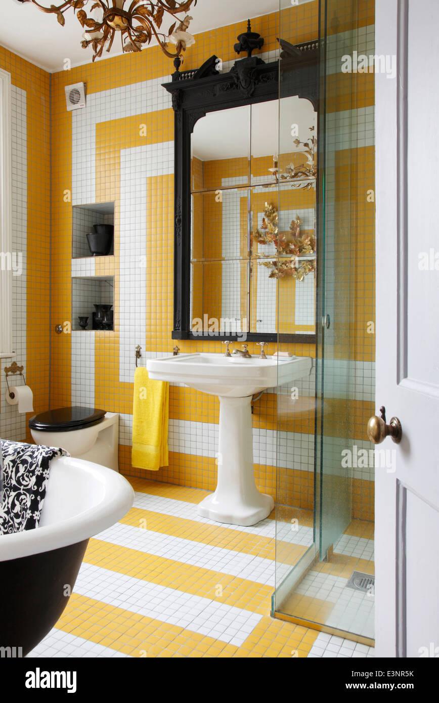 Salle de bains carrelée de blanc et jaune avec grand miroir ...