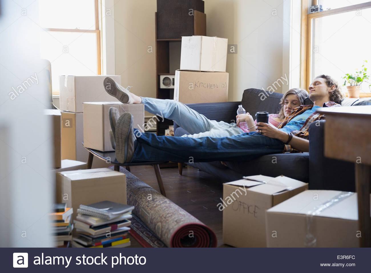 Couple relaxing on sofa entouré par des boîtes de déménagement Photo Stock