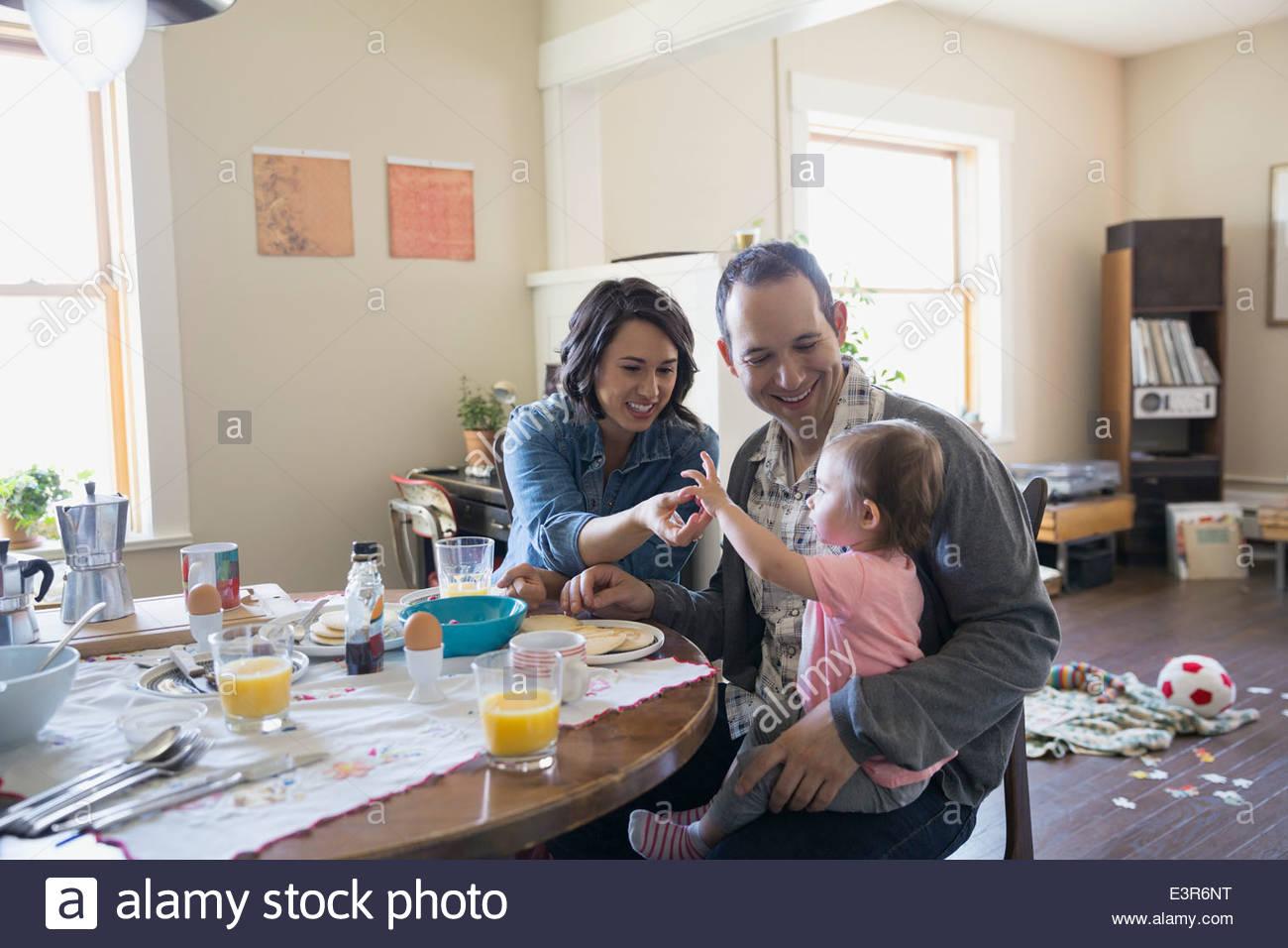 Jeune famille appréciant leur petit-déjeuner à table à manger Photo Stock