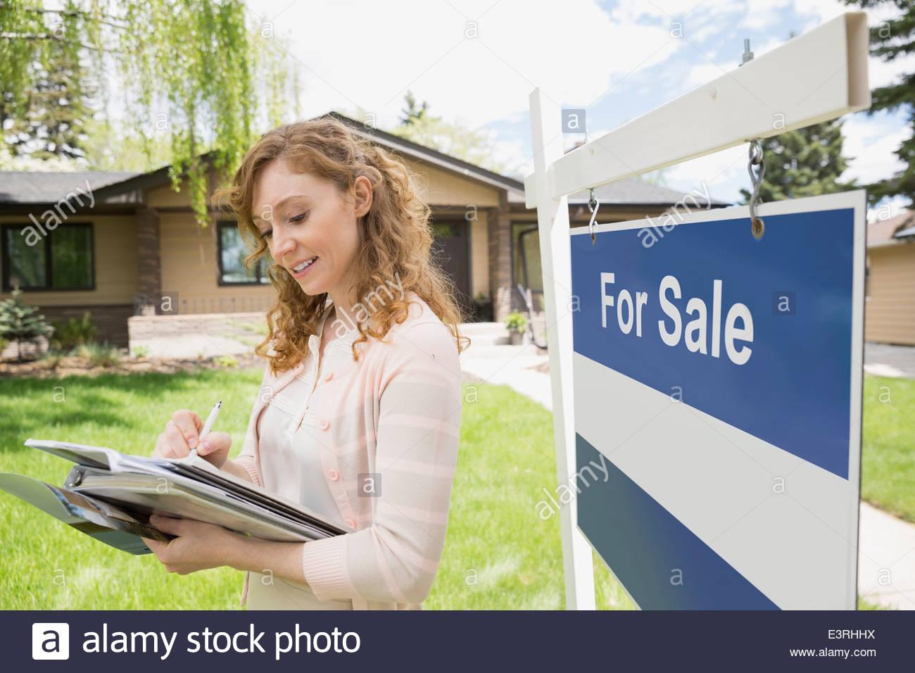 Contrôle de l'agent immobilier à côté de paperasserie For Sale sign Photo Stock