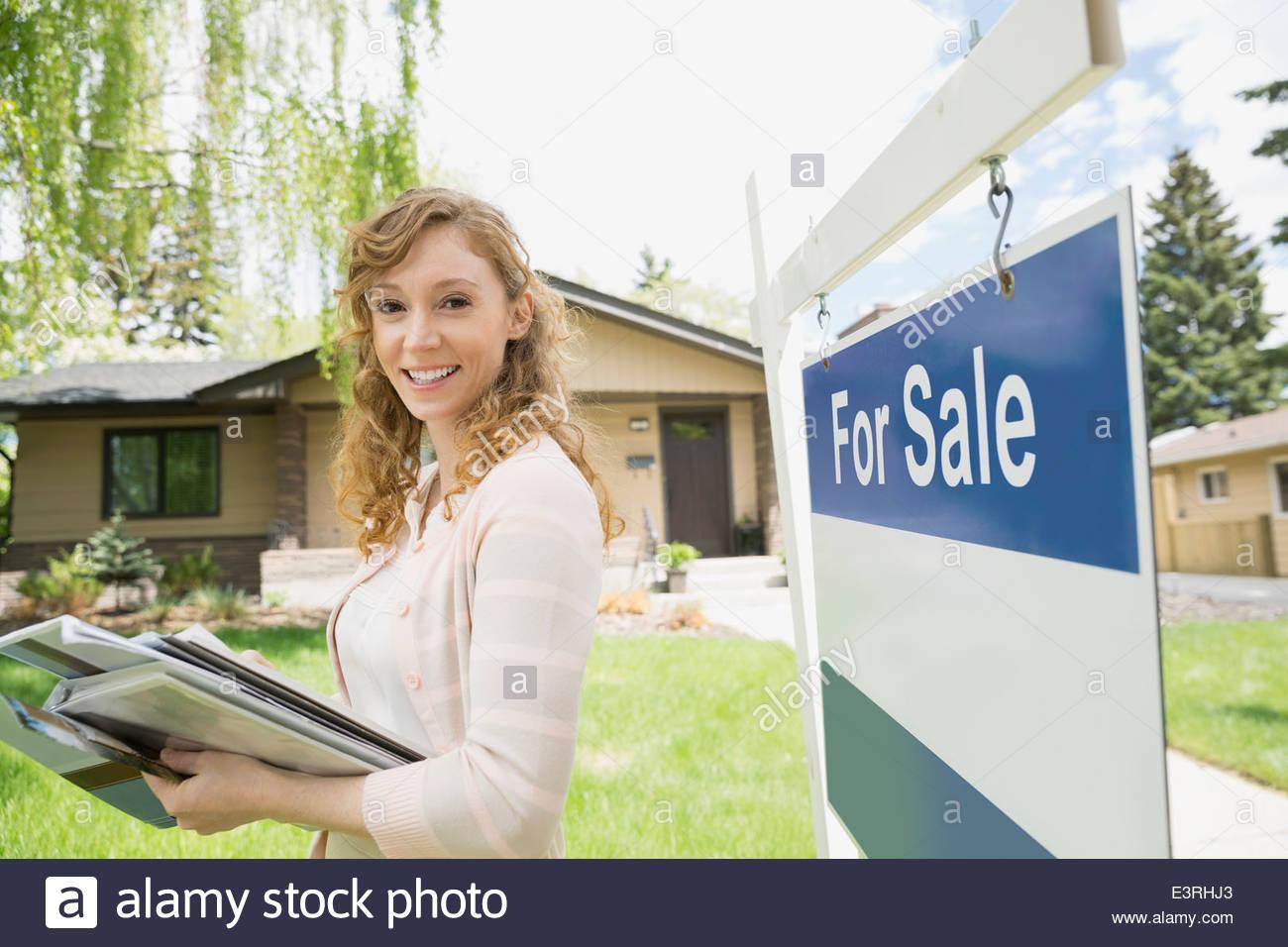 Portrait d'agent immobilier à côté de For Sale sign Photo Stock