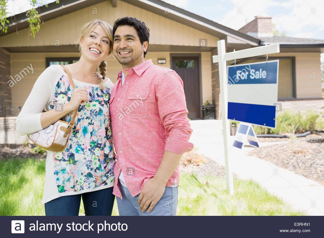 Couple smiling suivant pour For Sale sign Photo Stock