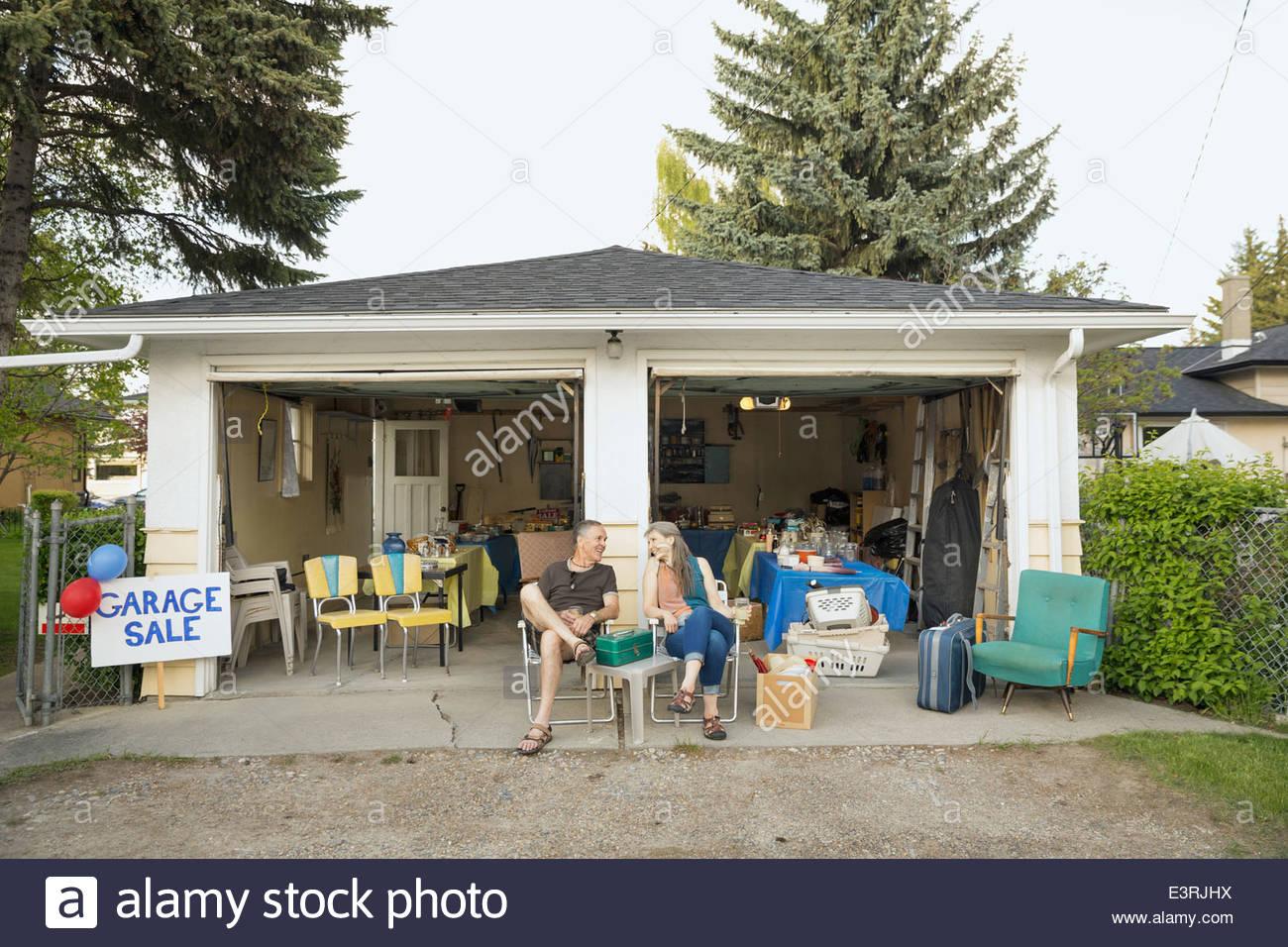 Couple assis à l'extérieur de vente de garage Photo Stock