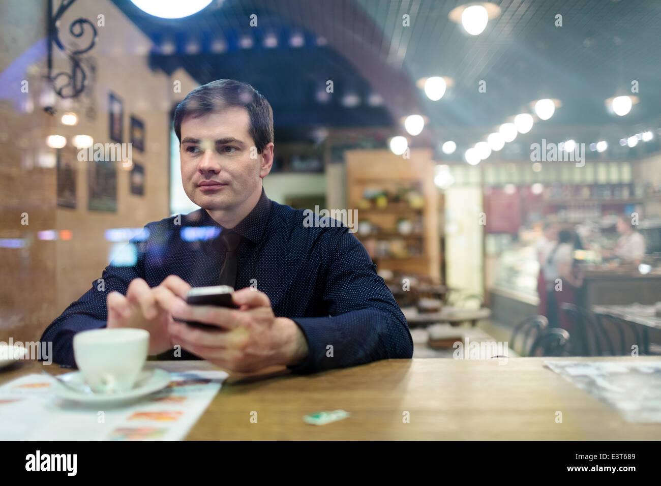 L'homme à la table texting Photo Stock