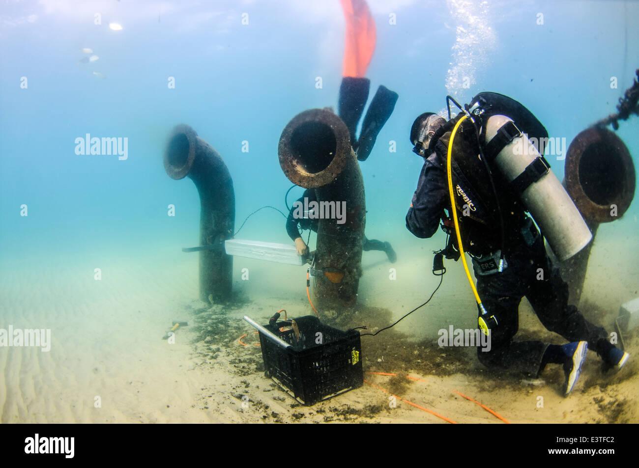 Les plongeurs commerciaux joindre une anode en zinc à un tuyau de décharge de la saumure Photo Stock