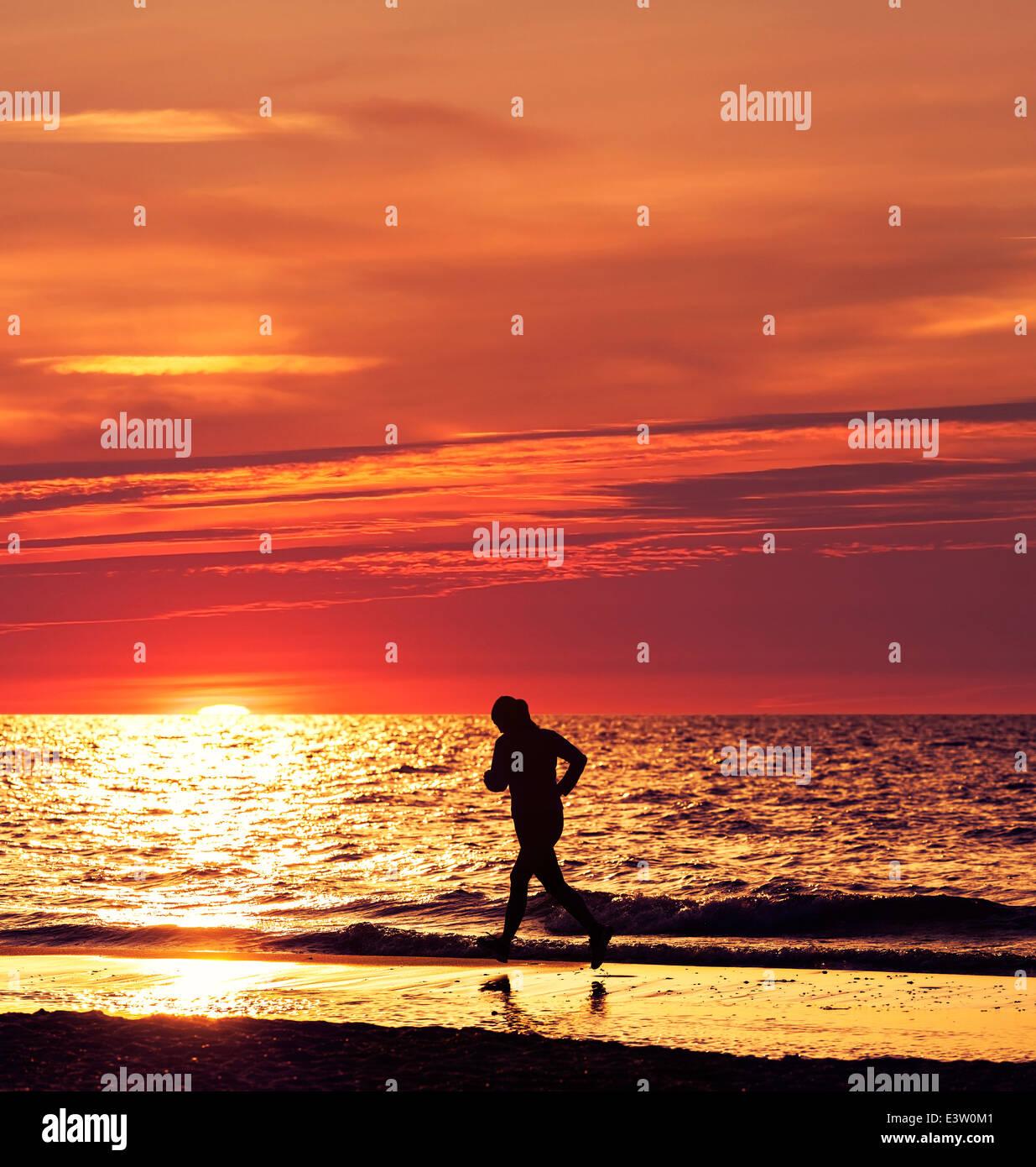 Femme tournant au beau coucher du soleil à la plage. Photo Stock