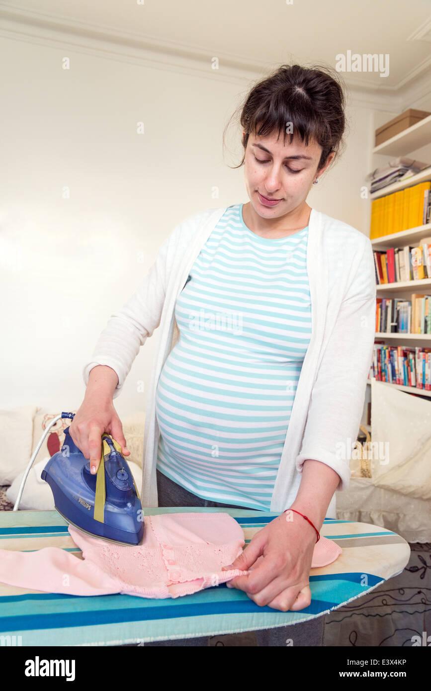 Repassage femme enceinte vêtements de bébé en prévision de l'arrivée de bébé, England, UK Banque D'Images