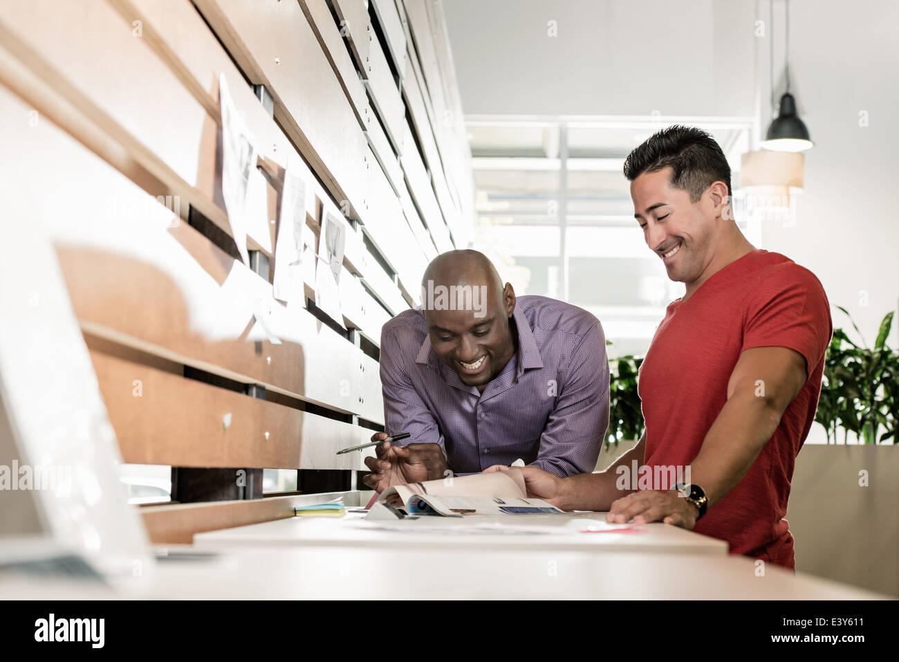 Deux hommes des collègues partageant un rire in office Photo Stock