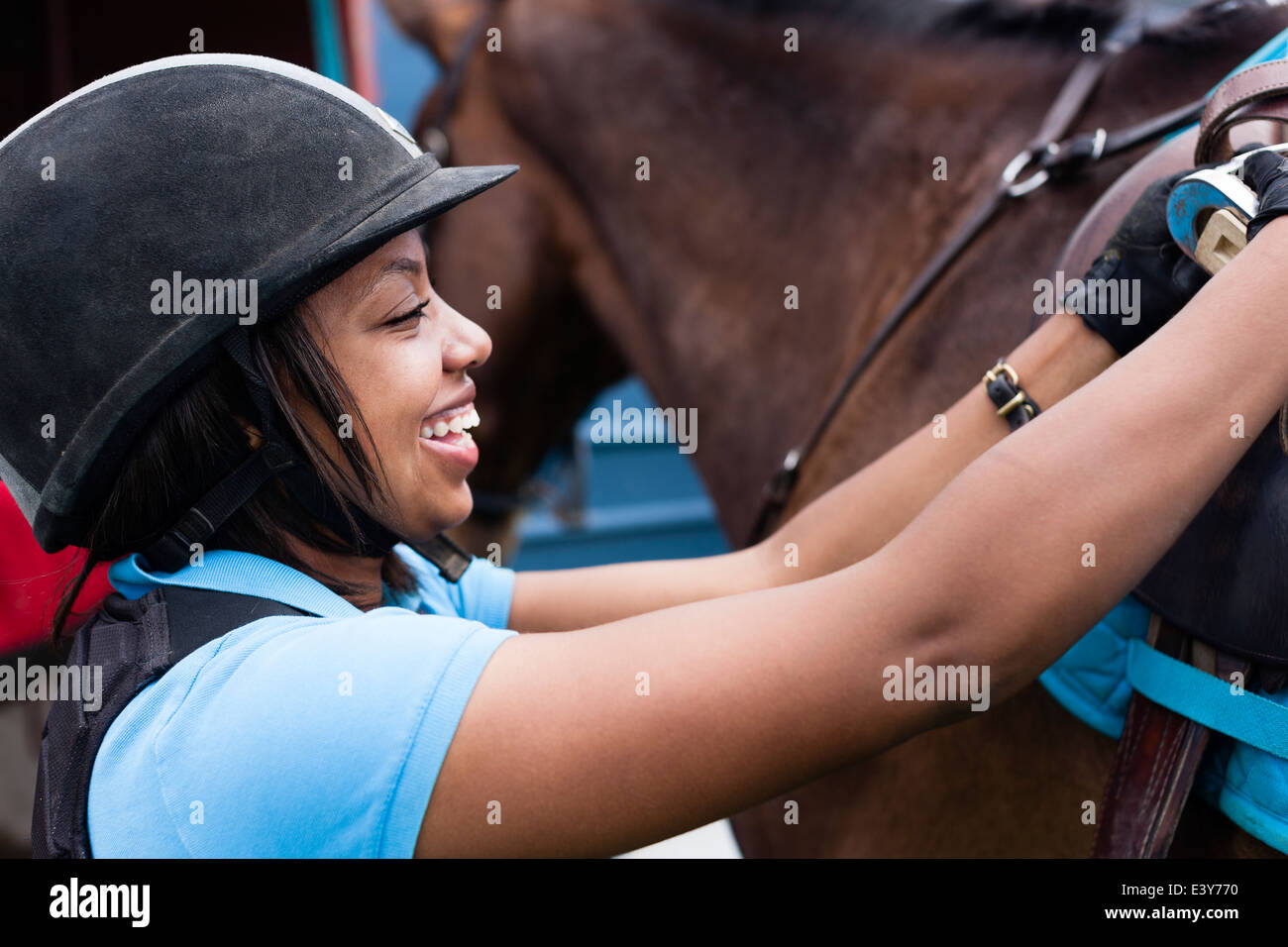 Close up of young woman putting saddle on horse Photo Stock