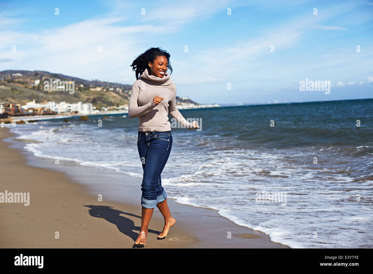 Jeune femme marchant pieds nus sur la plage, Malibu, California, USA Photo Stock