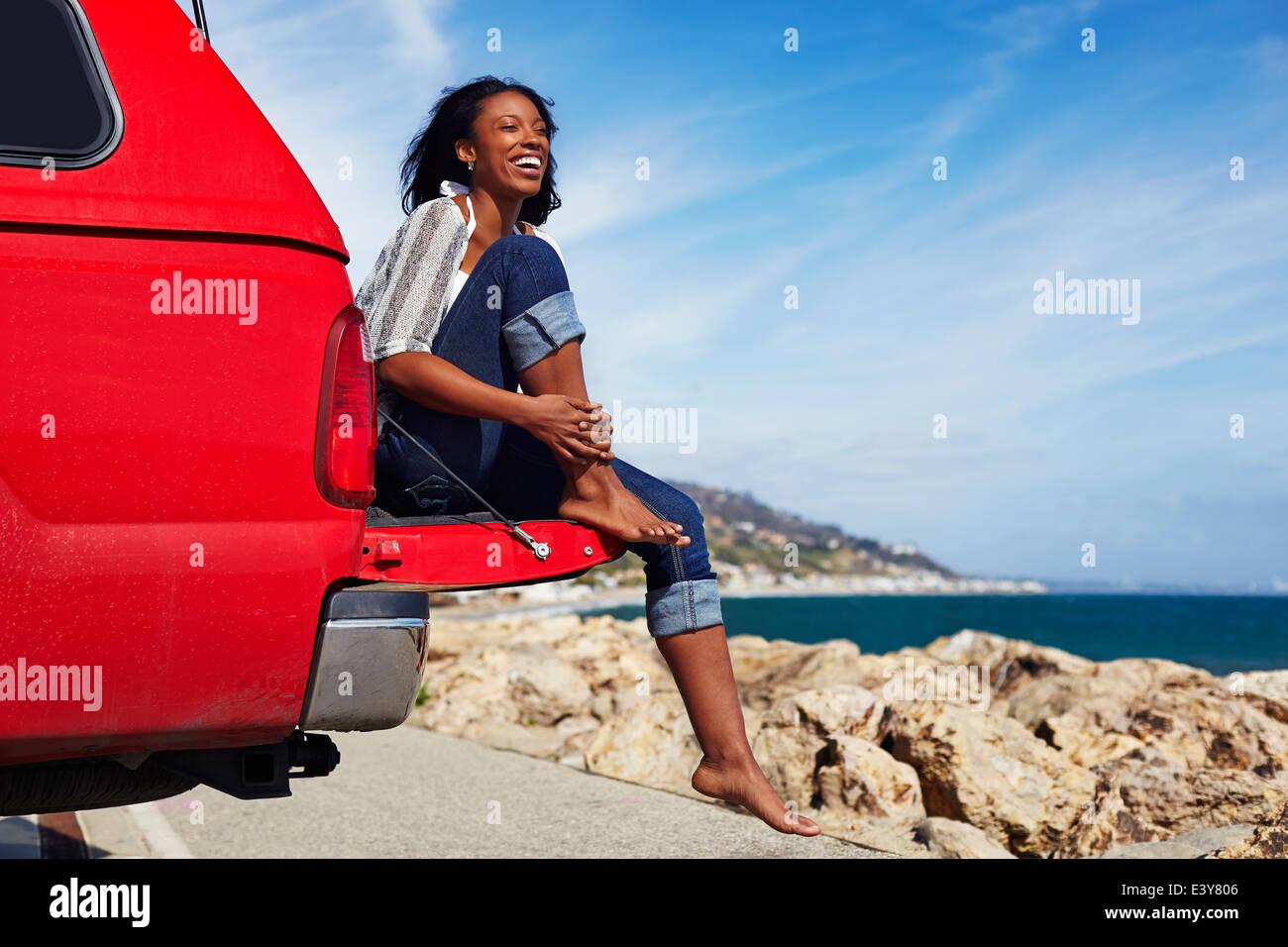 Jeune femme assise sur un capot de voiture, Malibu, California, USA Photo Stock