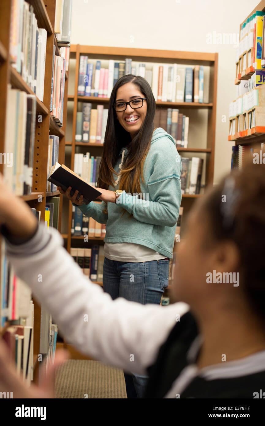 Les jeunes femmes choisissant books in library Photo Stock