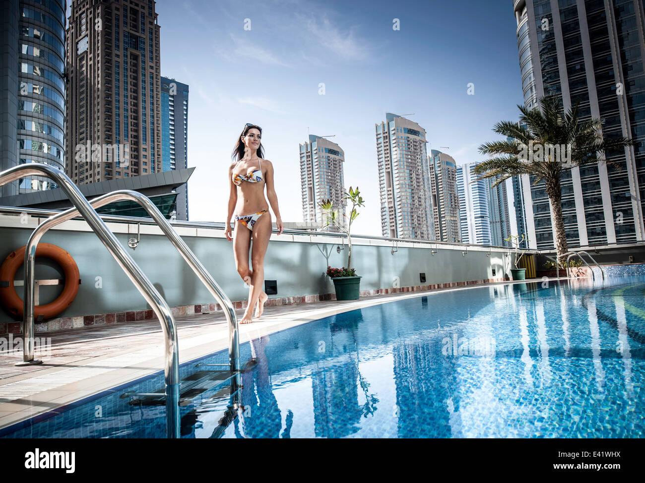 Young woman in bikini à la piscine sur le toit, Dubaï, Émirats Arabes Unis Photo Stock