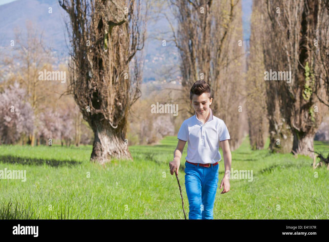 Un garçon de douze ans se promener avec bâton de marche Photo Stock