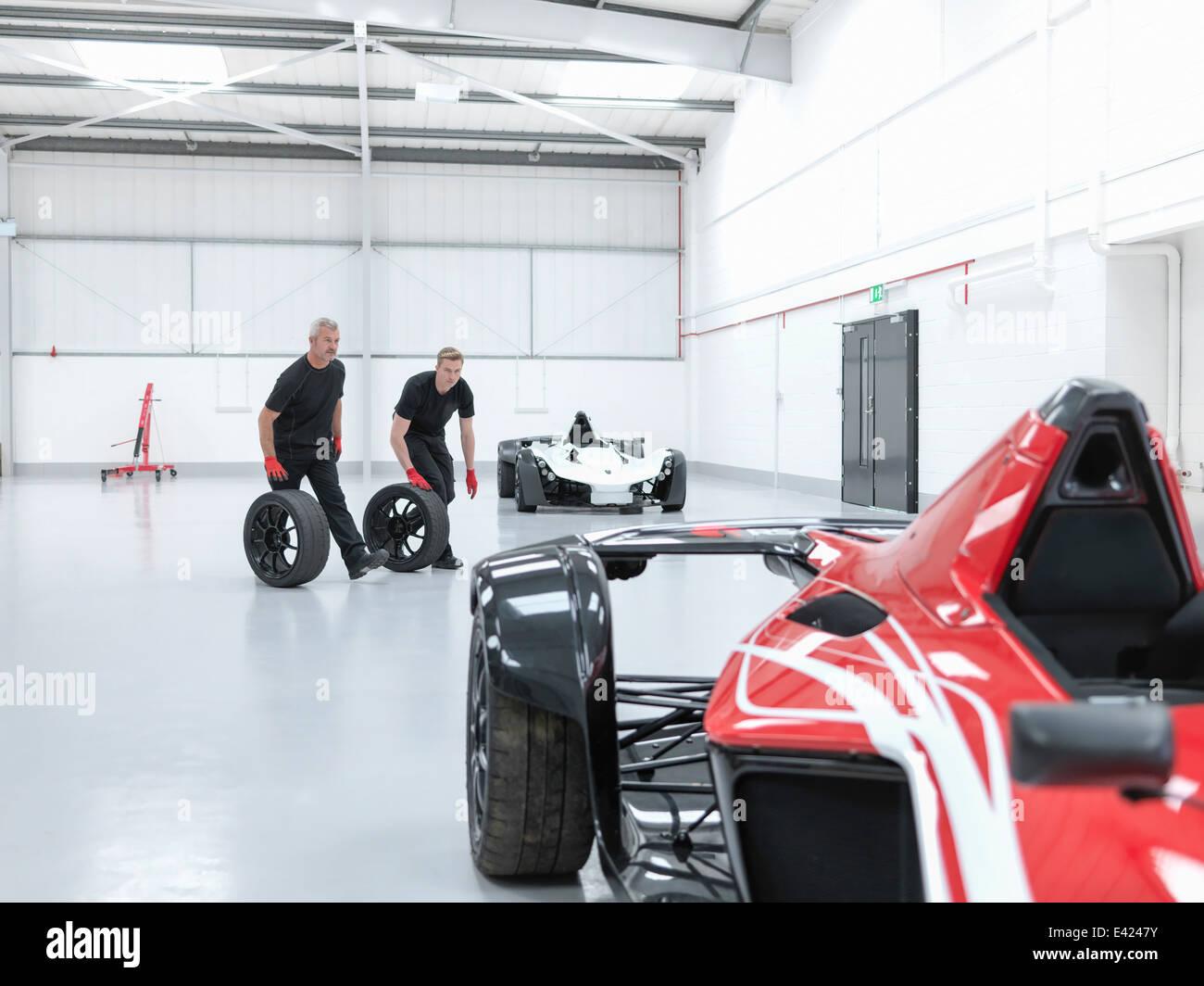 Les roues du matériel roulant d'ingénieurs près de supercar en usine de voiture de sport Photo Stock