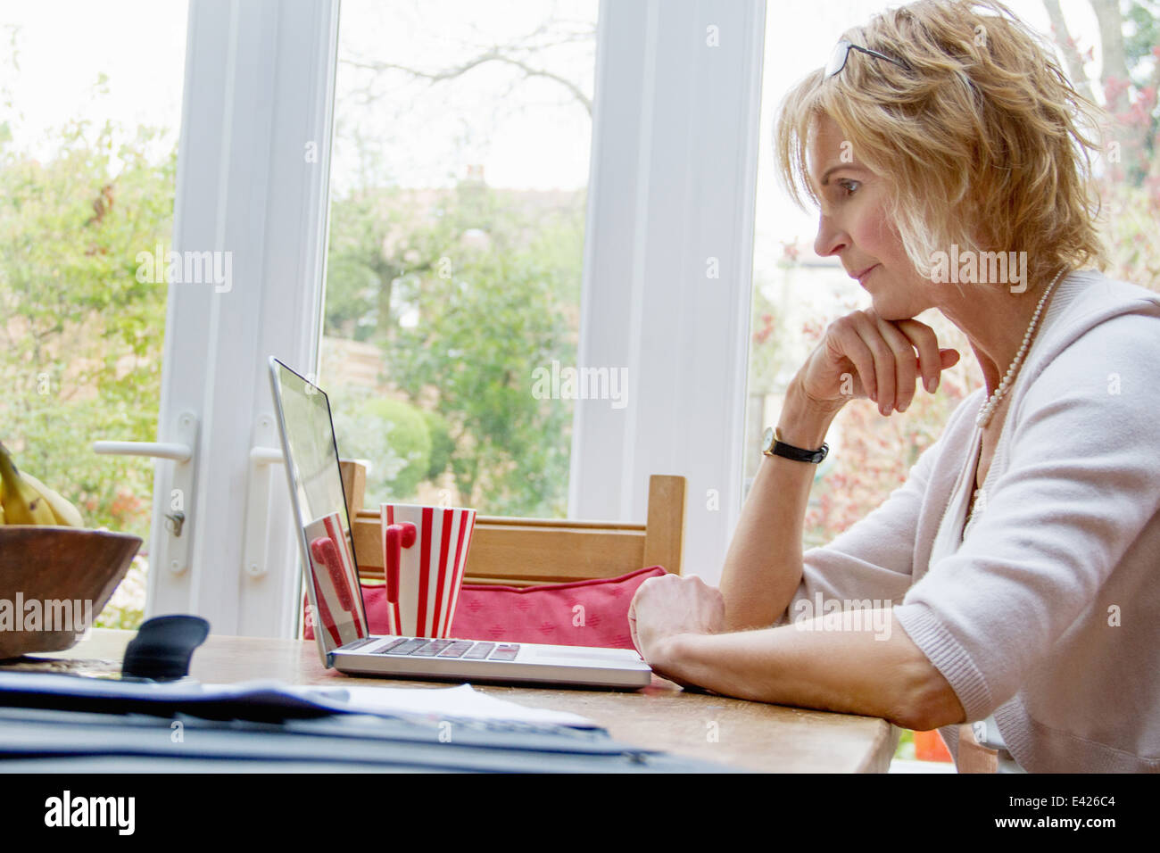 Mature Woman using laptop in kitchen Banque D'Images