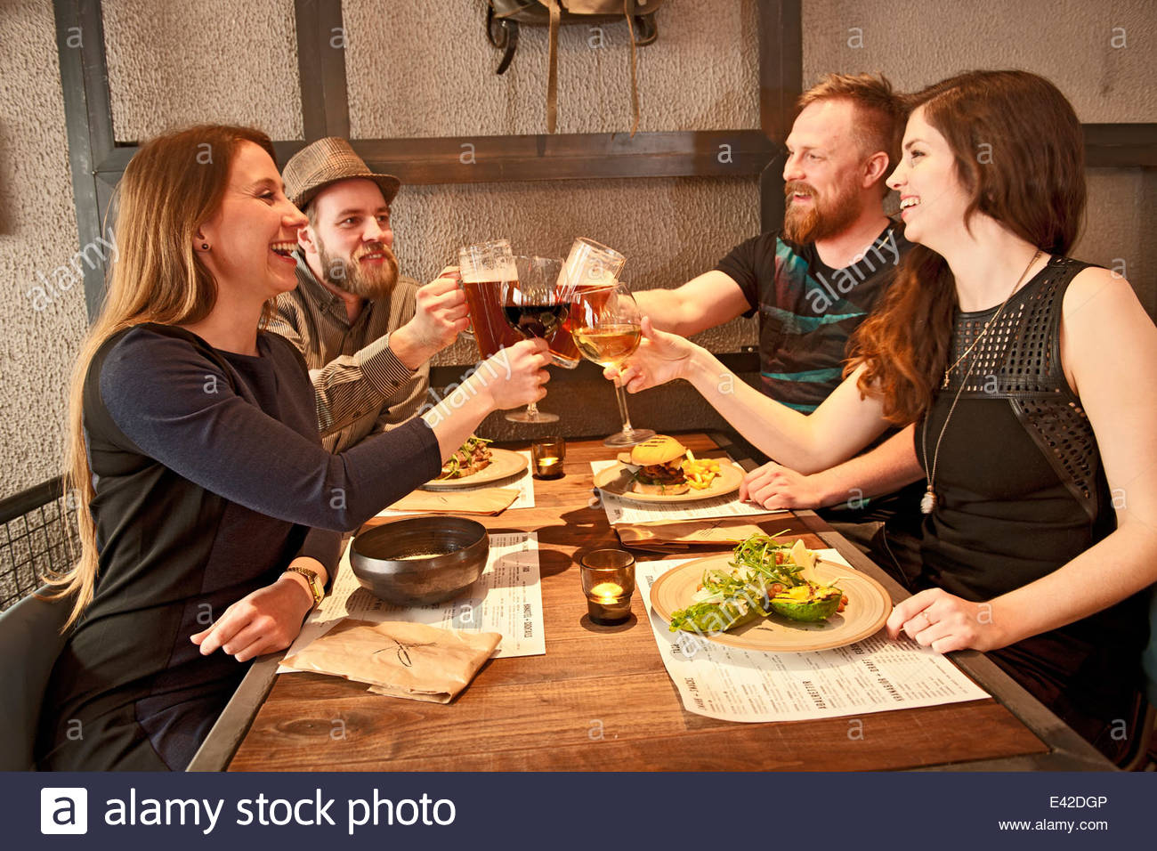 Hipster Friends toasting at bar Photo Stock