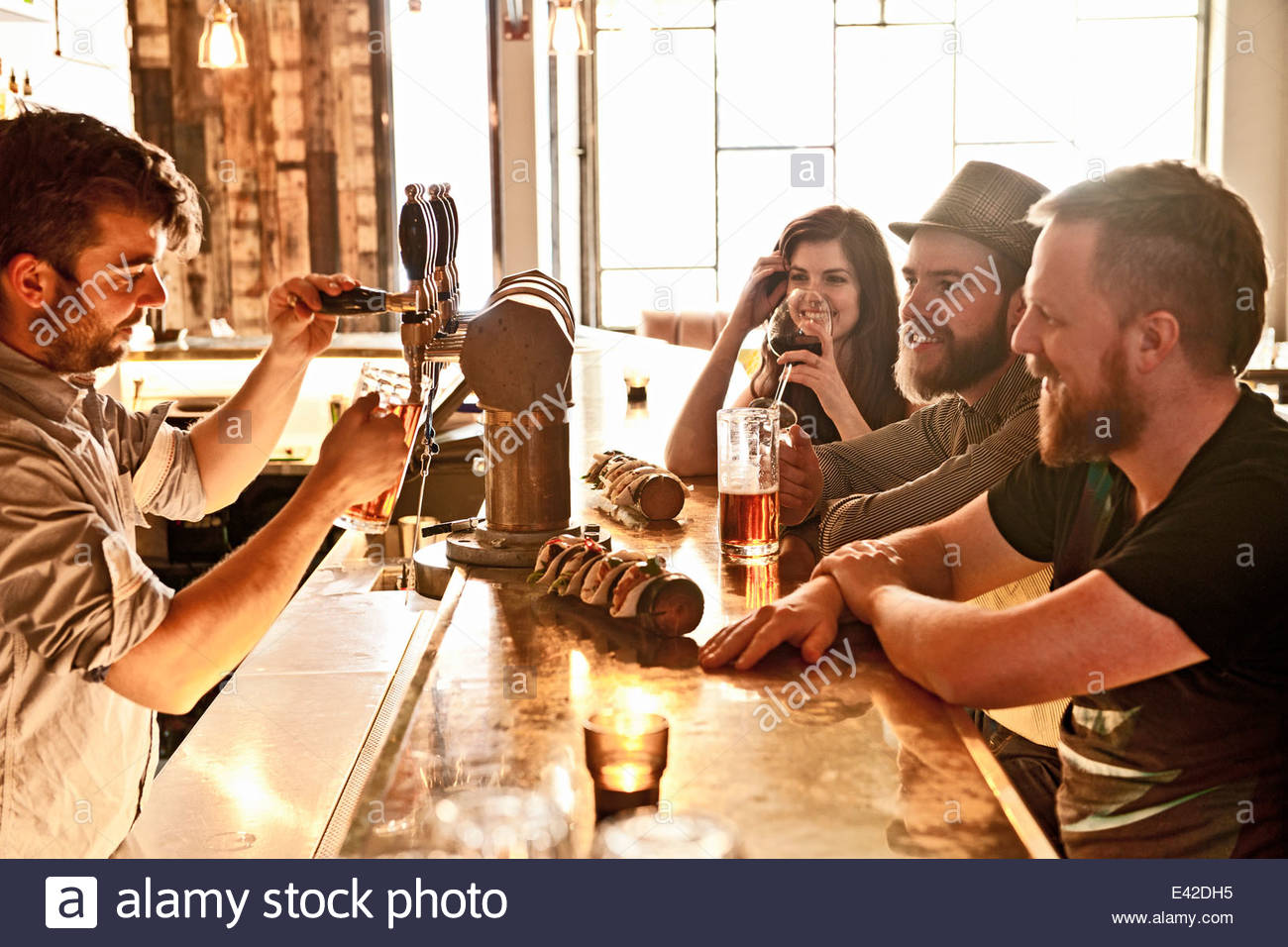 Les amis de boire une bière au bar branché Photo Stock