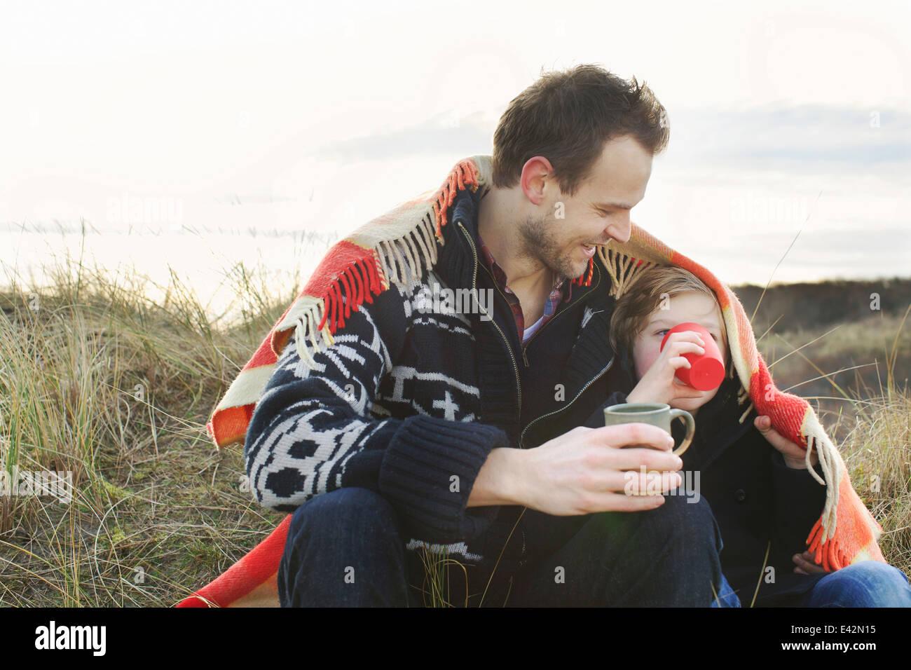 Smiling young man et fils enveloppés de couverture sur les dunes de sable Photo Stock