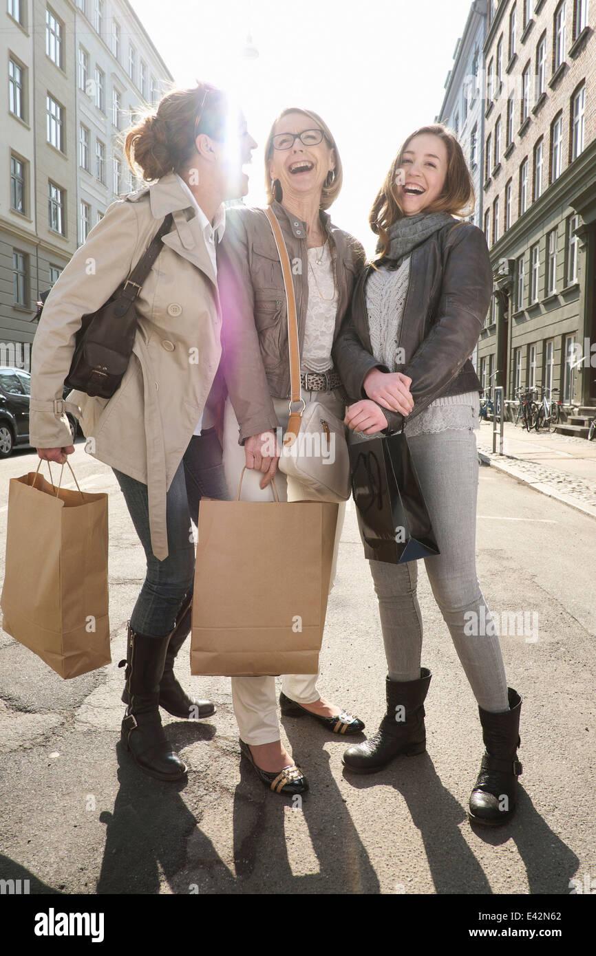 Trois femelles avec génération shopping bags on city street Photo Stock