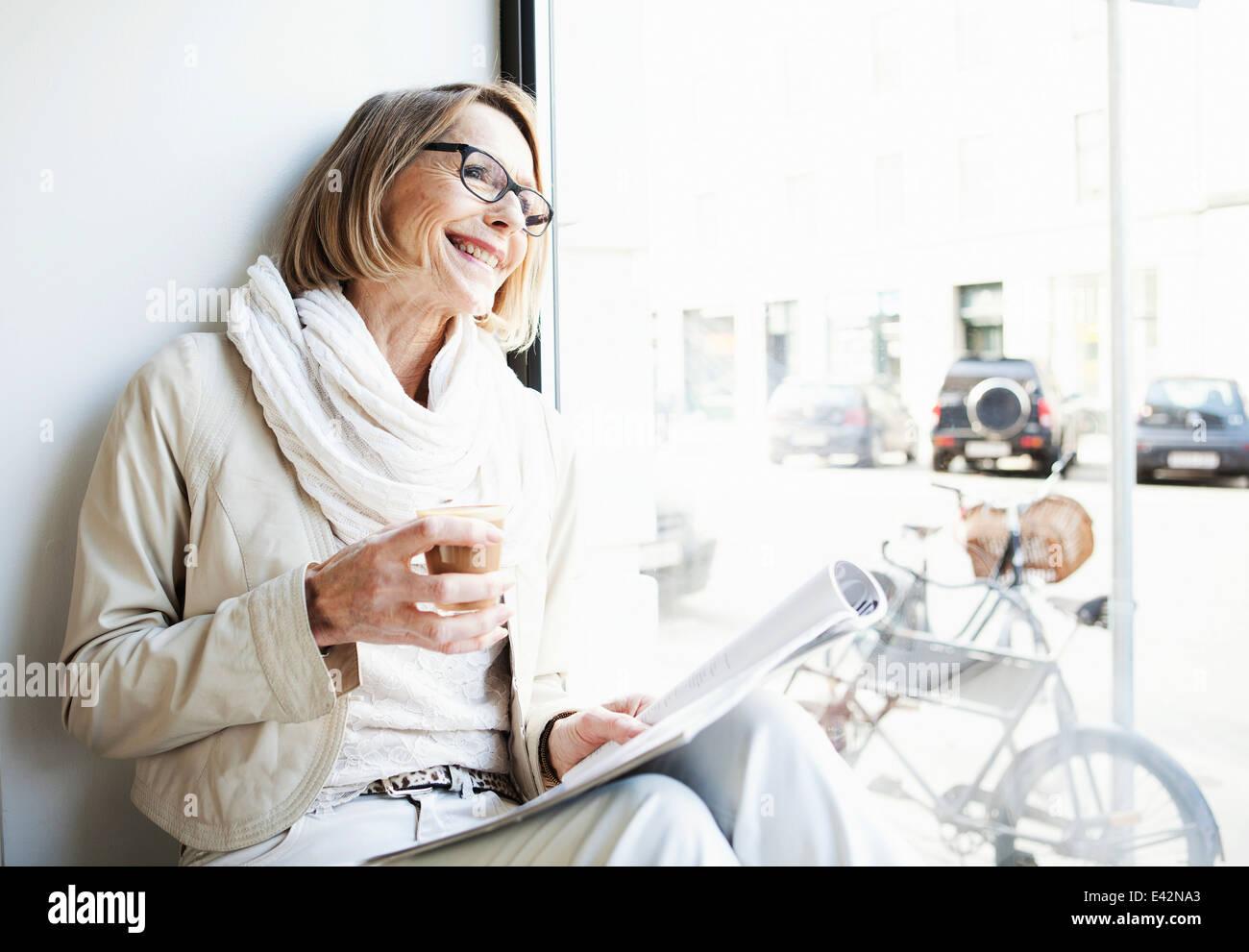 Senior woman having coffee in cafe un siège côté fenêtre Photo Stock