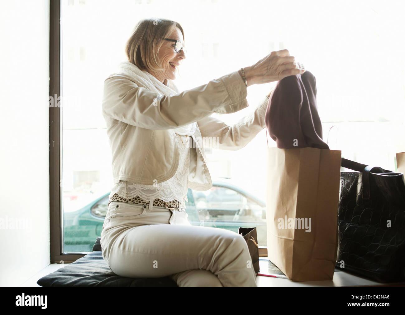 Senior woman admiring achats en boutique siège de fenêtre Photo Stock