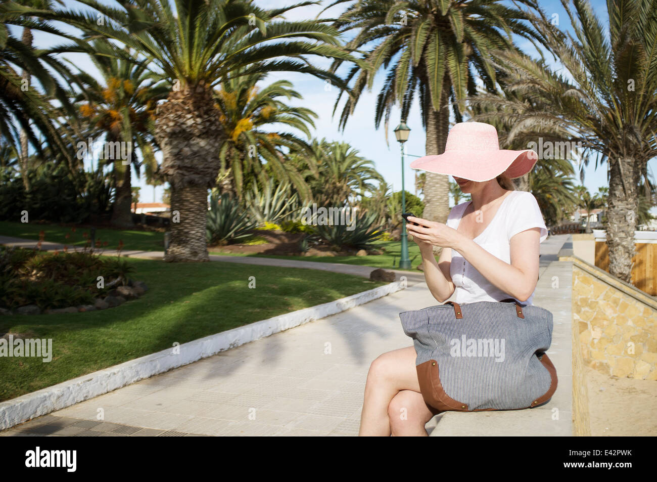Mid adult woman texting on smartphone in park gardens at coast Banque D'Images